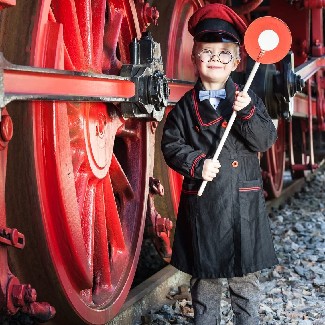 A young boy is standing next to the wheel of a large steam locomotive.
