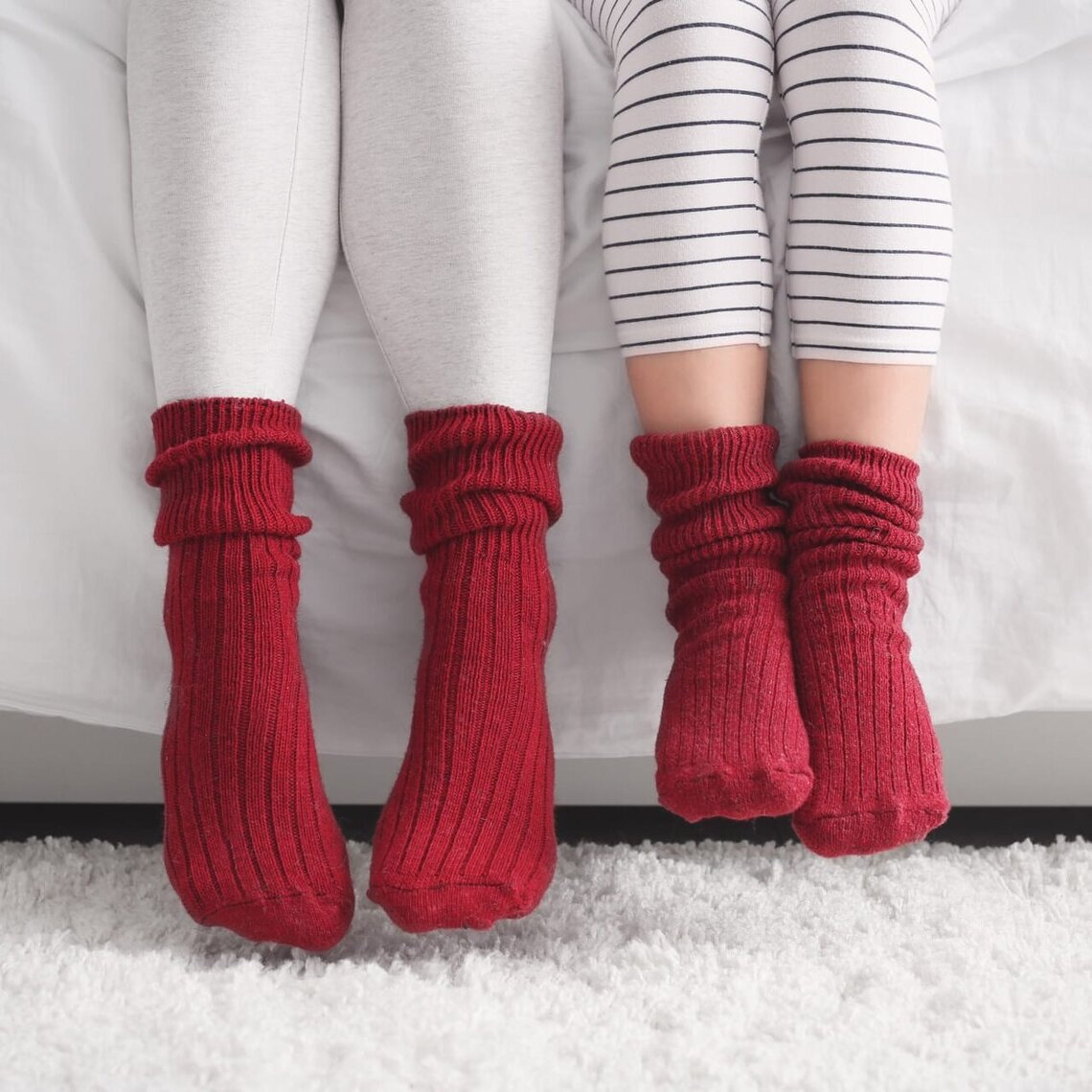 Two pairs of feet with warm socks are dangling from a couch.