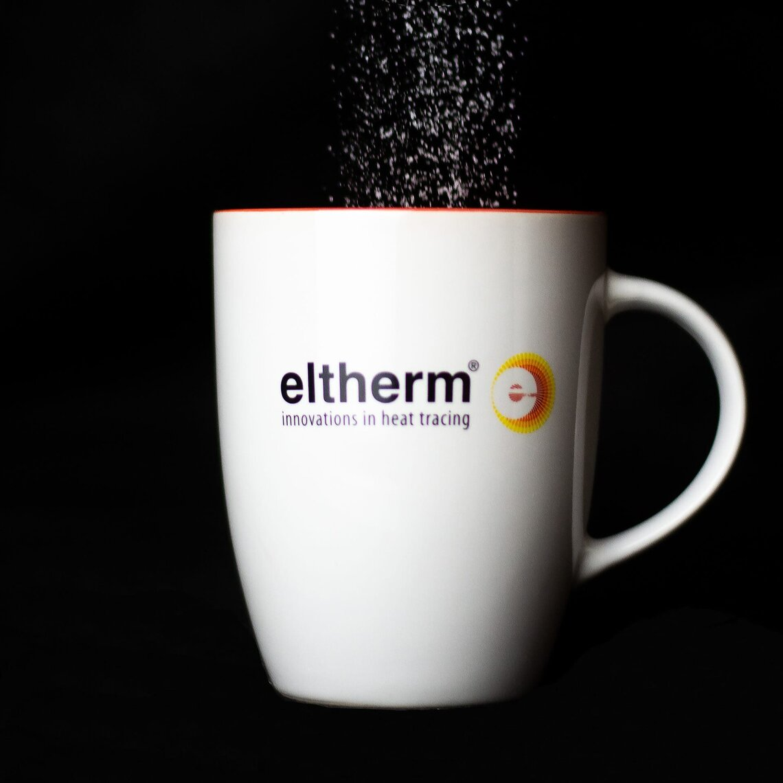 Sugar drizzles into a eltherm branded cup.